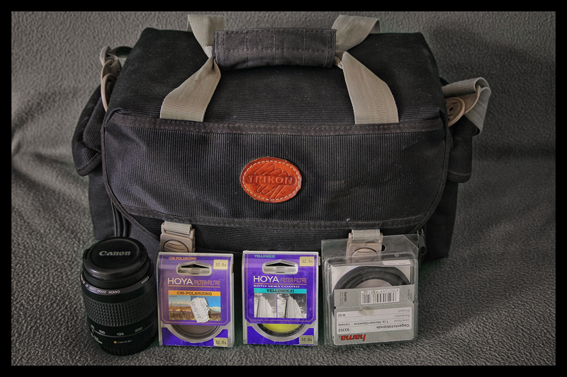 Trikon shoulder camera bag containing a Canon EF 80-200mm F/4.5-5.6 II, Hoya Cir-Polarizing filter, Hoya Yellow (K2) filter and a Hama rubber lens hood.